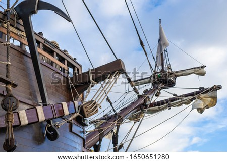 Anchor, masts and rigging of old pirate ship on background of cloudy blue sky. #1650651280
