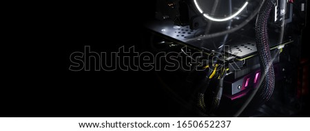 Close-up video card with backlight inside a computer on a black background. The concept of computer games, cyber sports and computer repair. Banner format, wallpapers.