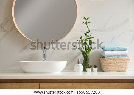Beautiful green plants near vessel sink on countertop in bathroom. Interior design elements #1650659203