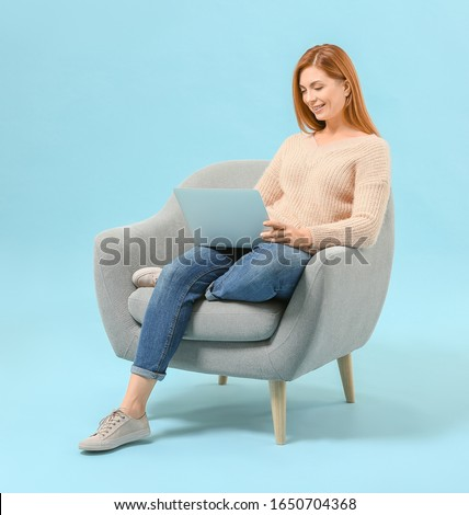 Beautiful woman with laptop sitting in armchair against color background