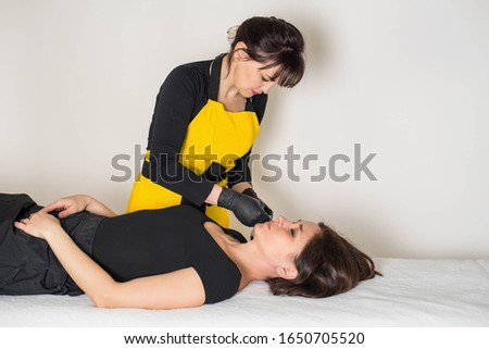 Cosmetologist is a professional with a patient in the office of.Sugar hair removal from woman body. Wax epilation spa procedure. Procedure beautician female. Mustache. #1650705520