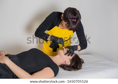 Cosmetologist is a professional with a patient in the office of.Sugar hair removal from woman body. Wax epilation spa procedure. Procedure beautician female. Mustache. #1650705526