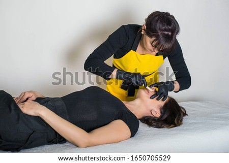 Cosmetologist is a professional with a patient in the office of.Sugar hair removal from woman body. Wax epilation spa procedure. Procedure beautician female. Mustache. #1650705529