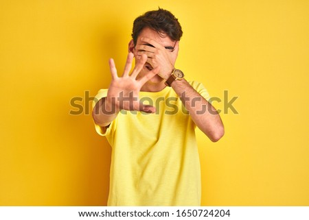 Teenager boy wearing yellow t-shirt over isolated background covering eyes with hands and doing stop gesture with sad and fear expression. Embarrassed and negative concept. #1650724204