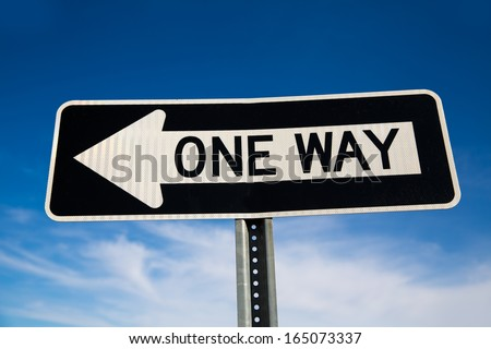 One way arrow sign in USA under blue sky