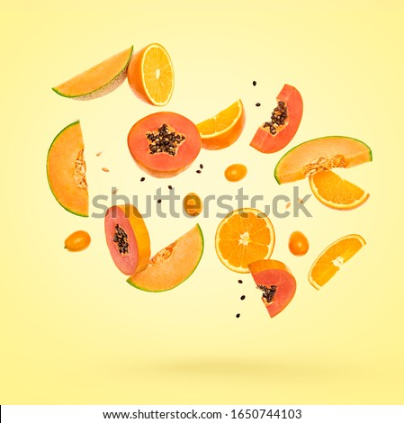 Flying fruits healthy summer background. Papaya, orange, melon. Levitation, falling fly fruit. Tropical creative concept. Colorful fruity summertime orange vivid design on yellow #1650744103