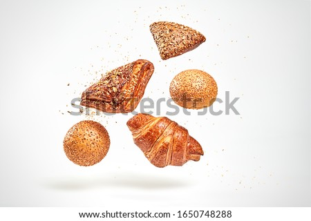 Croissant bun brioche cake flying in air. Fresh baked cookie with sesame, sunflower seed falling on white. Delicious french grain baking. Levitation, fly bread bakery products cafe concept Royalty-Free Stock Photo #1650748288