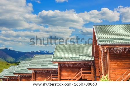 wooden cabin cottages rustic architecture building foreground and vivid highland landscape background space with blue sky and white clouds travel and tourism concept advertising picture copy space