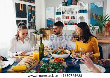 family sits at the dining table and having dinner party at home. #1650795928
