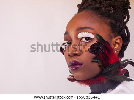 Portrait of a beautiful young African woman. Studio with white background. Face close up. Make up with lashes made of feathers. Fashion style. #1650835441