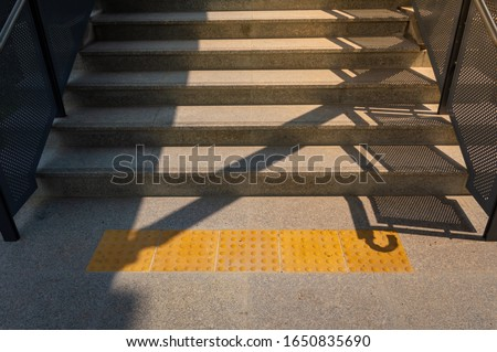 Stairs in sky train stationwith disabled walking path for blind people.Sidewalk guide or tactile paving floor for blind people, Block tactile paving for blind handicap. #1650835690