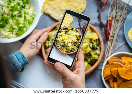 Take picture of food with phone at kitchen. Smartphone photo of vegetables, potato, cabbage stew. Vegan healthy dietary food.