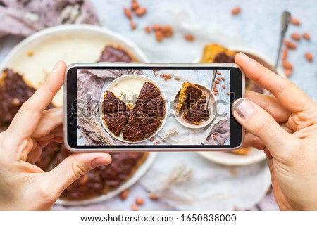 Take picture of food with phone at kitchen. Smartphone photo of dessert. Chocolate carrot pie, cake. Vegan healthy dietary food.