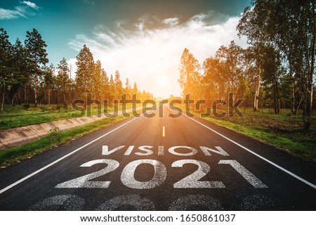Vision 2021 written on highway road in the middle of empty asphalt road at golden sunset and beautiful blue sky. Concept for new year 2021. #1650861037