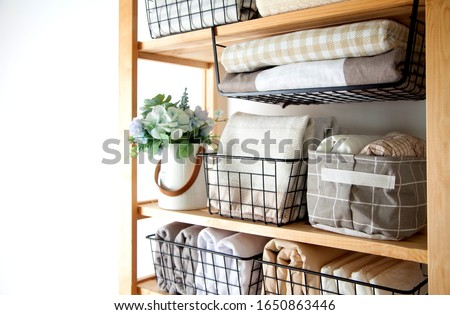 Spring cleaning of closet. Vertical tidying up storage. Neatly folded bed sheets in the metal black baskets for wardrobe. Nordic style. #1650863446