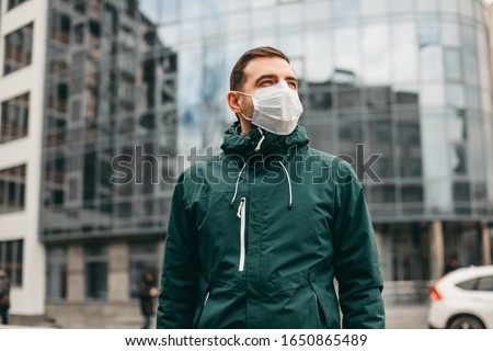 portrait of brunette man in a surgical bandage on a background of a modern building, coronavirus, illness, infection, quarantine, medical mask #1650865489
