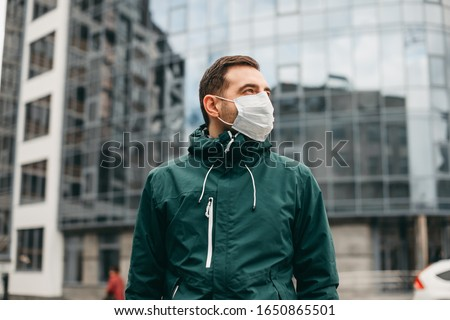 portrait of brunette man in a surgical bandage on a background of a modern building, coronavirus, illness, infection, quarantine, medical mask #1650865501