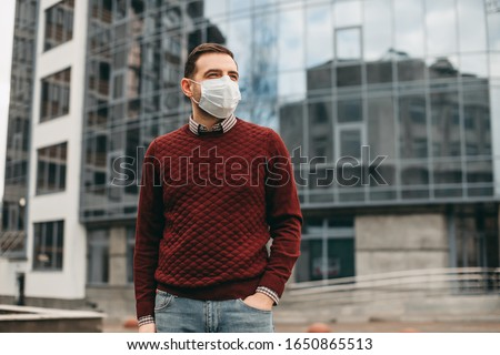 portrait of brunette man in a surgical bandage on a background of a modern building, coronavirus, illness, infection, quarantine, medical mask Royalty-Free Stock Photo #1650865513