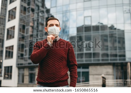 portrait of brunette man in a surgical bandage on a background of a modern building, coronavirus, illness, infection, quarantine, medical mask #1650865516
