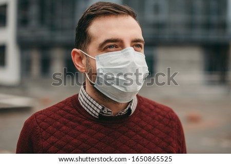 portrait of brunette man in a surgical bandage on a background of a modern building, coronavirus, illness, infection, quarantine, medical mask Royalty-Free Stock Photo #1650865525