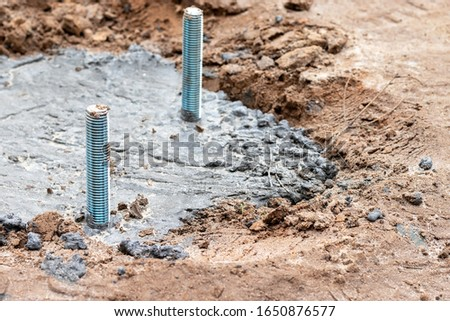 Concrete pouring and preparation of anchors for installation of a lighting column or a billboard. Concrete foundation in the ground with two anchor bolts. Selective focus. Closeup view #1650876577