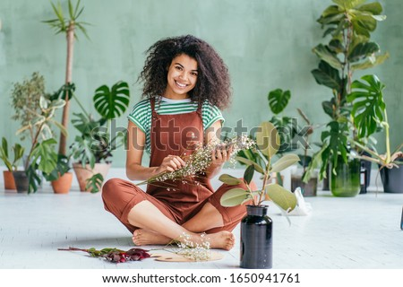 Young woman cultivating home plants.Small business.Sensual mixed race female florist with flowers in hands against background of indoor plants. Life lover, zero waste, inspiration, summer mood concept #1650941761
