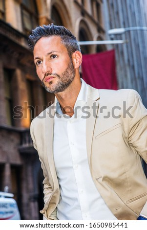 Young handsome European Man with beard traveling in New York City. Young guy wearing beige blaze, white shirt, walking on narrow vintage street with banners, looking forward, seriously thinking. #1650985441
