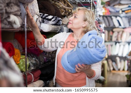 mature woman purchaser  choosing soft plaids in the textile shop #1650995575