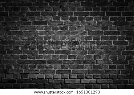 An old black bricks wall surface abstract pattern background. Background of old vintage brick wall with vignetting.