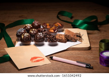Gold mint and white chocolate ball, coins and dark chocolate for valentine event on white paper and flat wooden plate with lipstick kiss pink pen green ribbon on wood table stock photo #1651042492