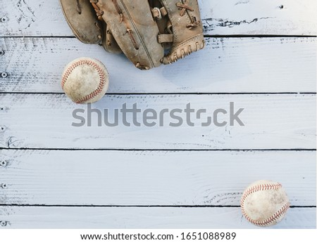 Old baseball equipment with top view of rustic balls on wood texture background.  Copy space for sports team by glove with ball. #1651088989