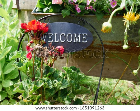 Inviting metal Welcome sign in the entry of a house garden