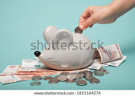 A child puts a coin in a piggy bank with a mouse #1651164274