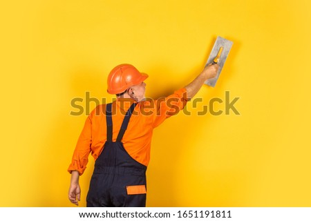 plaster trowel spatula on yellow drywall plasterboard. Plasterer in working uniform plastering wall indoor. man with spatula. process of applying layer of putty. Plastering tools for plaster. #1651191811