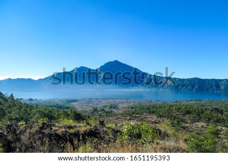 An idyllic view from the top of Mount Batur on Mount Agung and the Danau Batur lake. There is a pathway along Batur volcano's rim. Volcanic landscape of Bali, Indonesia. Island hiking. #1651195393