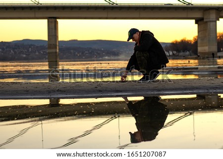 Troubled young man with baseball cap in squat, under the bridge on the sandy river bed after the river has dried up after a dry winter. Sunset. Reflection in the water. #1651207087