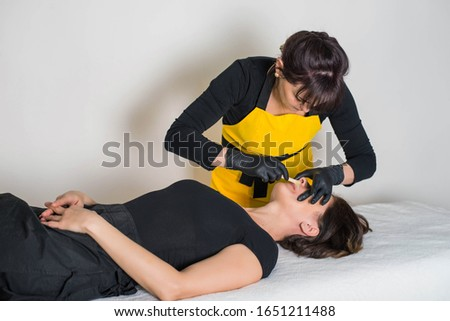 Cosmetologist is a professional with a patient in the office of.Sugar hair removal from woman body. Wax epilation spa procedure. Procedure beautician female. Mustache. #1651211488
