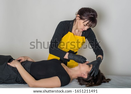 Cosmetologist is a professional with a patient in the office of.Sugar hair removal from woman body. Wax epilation spa procedure. Procedure beautician female. Mustache. #1651211491