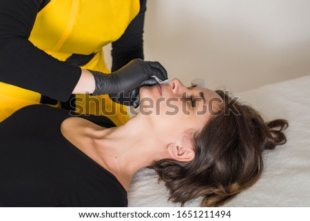 Cosmetologist is a professional with a patient in the office of.Sugar hair removal from woman body. Wax epilation spa procedure. Procedure beautician female. Mustache. #1651211494