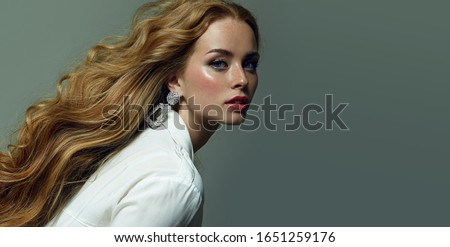 Beautiful young red-haired and fair-skinned girl with freckles posing in the studio on a gray background. Blue eyes.