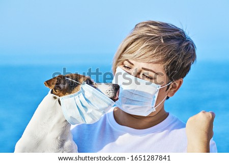 Woman in protective face mask looking at dog wearing medical mask too. Chinese Coronavirus disease COVID-19 is dangerous for pets concept #1651287841
