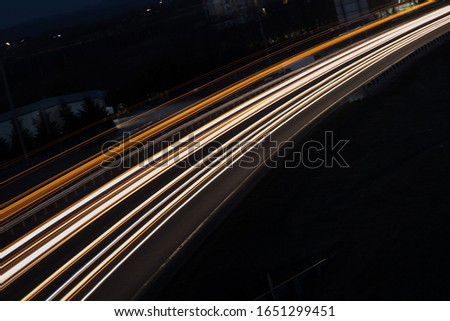 A long exposure of a highway with white and yellow lights going from corner to corner of the frame. #1651299451