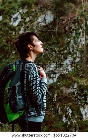 Young hiker takes a rest during his ascent to the mountain. Contemplate the landscape. healthy life concept #1651322734
