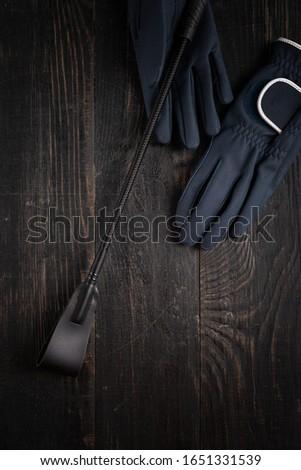 Items of equipment of horse jockey, jockey. Helmet, gloves, whip on black table