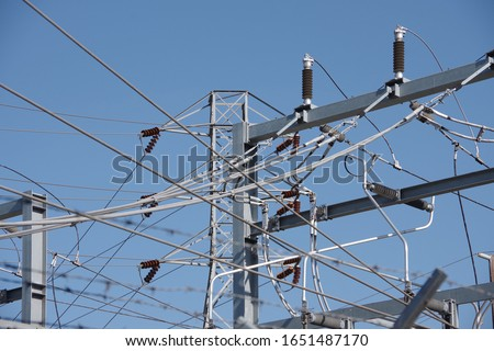 Close-up sectional view of parts of an electricity substation with an electricity distribution tower and blue sky behind #1651487170