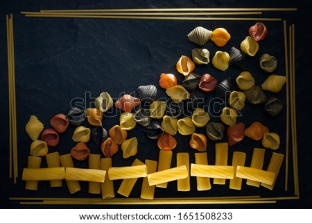 Uncooked pasta close-up. Abstract picture of pasta, vermicelli and spaghetti of different types in a frame on a black background