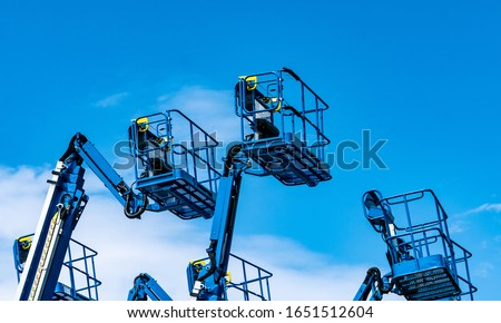 Articulated boom lift. Aerial platform lift. Telescopic boom lift against blue sky. Mobile construction crane for rent and sale. Maintenance and repair hydraulic boom lift service. Crane dealership.  #1651512604