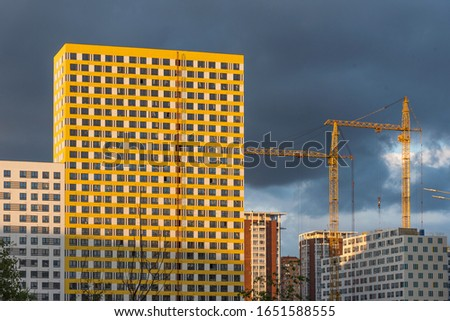 Construction in progress, construction of a modern new residential complex and cranes at sunset against a dramatic sky. Modern new residential complex. #1651588555