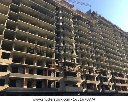 Construction work is underway at a fixed plaza, a crane is operating. High-rise construction of a concrete-brick house on a background of blue sky. Industrial background #1651670974