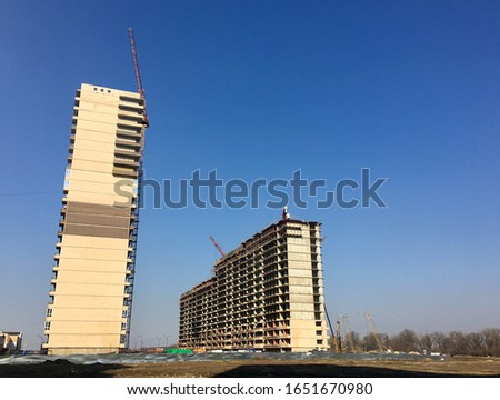 standing plaza in the distance, it is under construction, a crane is working. High-rise house construction over blurred natural blue sky background. Industrial background #1651670980